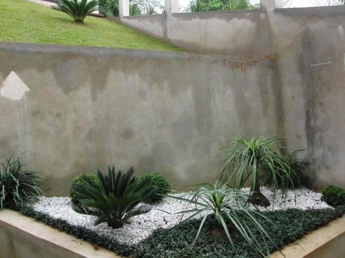 Jardim planejado com pedras brancas e grama preta