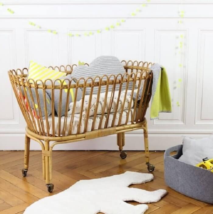 Quarto de bebê com berço de vime e almofadas decorativas