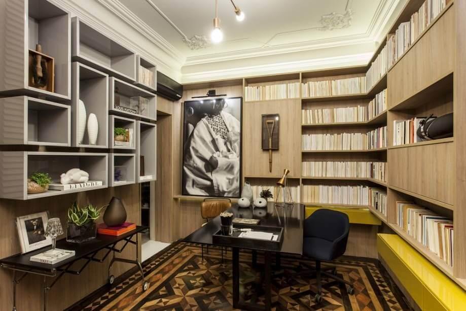 biblioteca e escritório com nichos de madeira cinzas