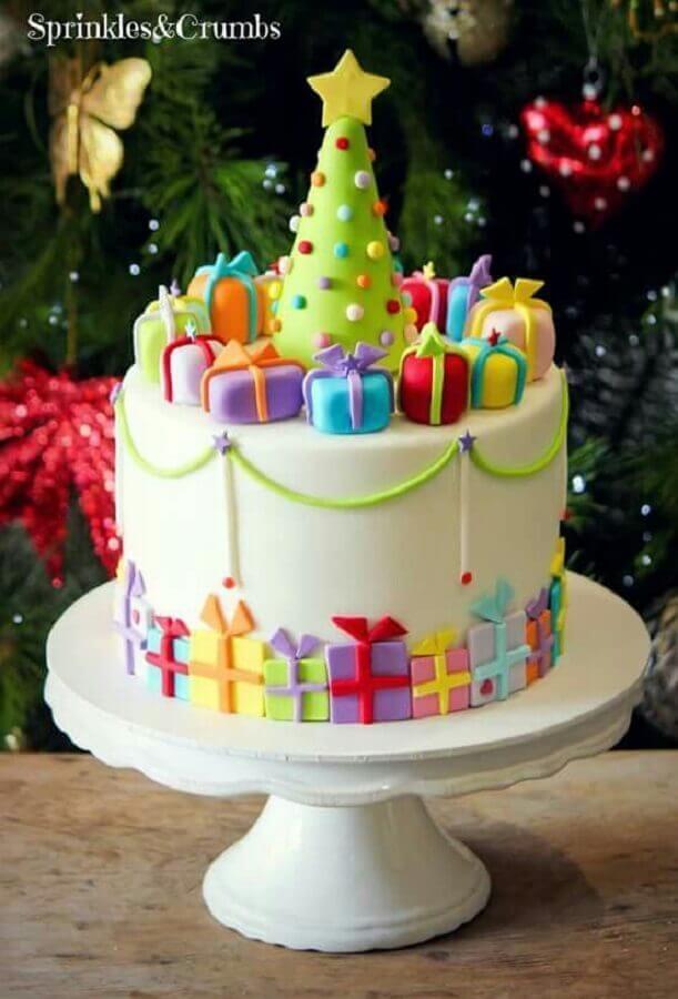 bolo de natal decorado com pasta americana com caixinhas de presentes coloridas e pequena árvore de natal no topo Foto Sprinkles & Crumbs