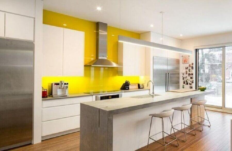 cozinha amarela e branca ampla decorada com ilha de cimento queimado Foto Notey