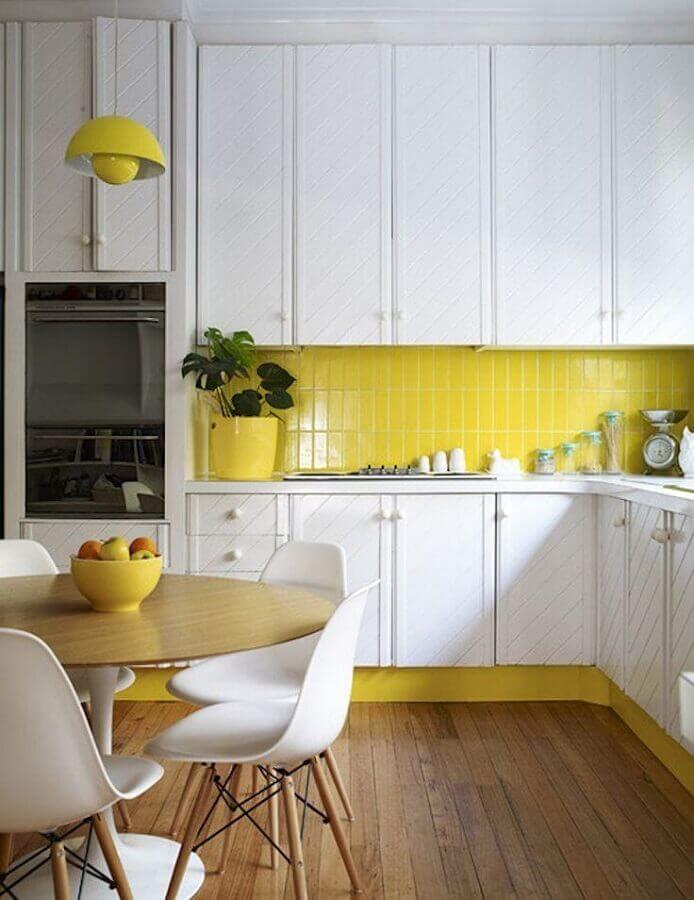 cozinha amarela e branca decorada com mesa redonda e armários planejados Foto Homedit