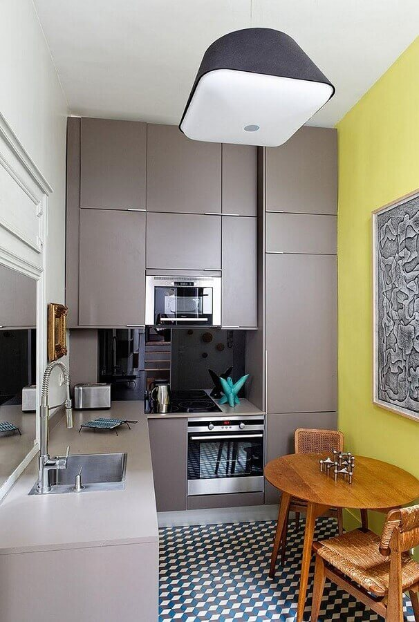 cozinha cinza e amarela decorada com armários planejados e mesa redonda de madeira Foto HomeServe