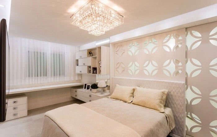 Quarto de casal em tons neutros decorado com lustre de cristal