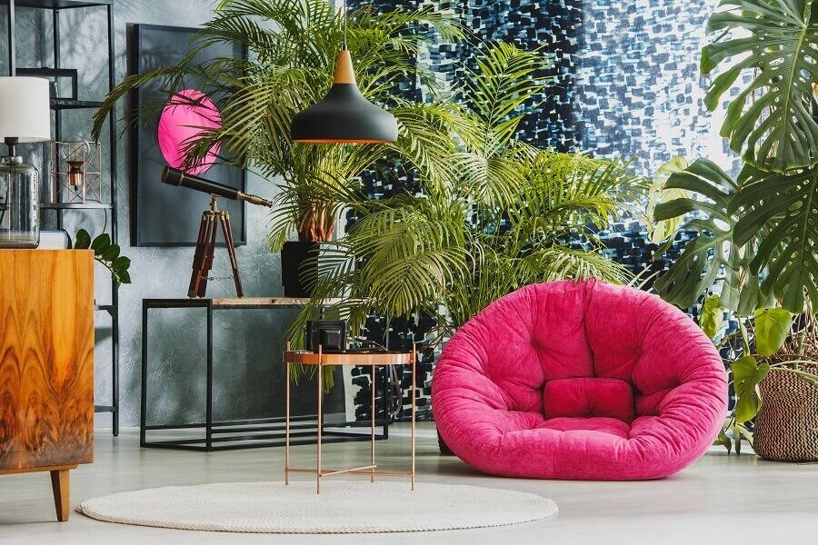 decoração para ambientes com vários vasos de plantas e puff rosa