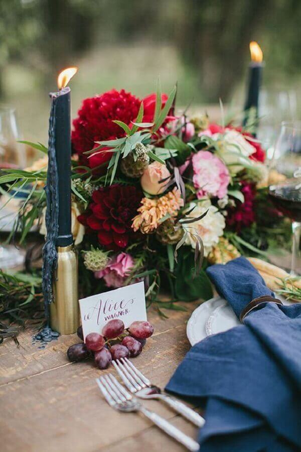 decoração para mesa de festa com castiçal dourado e vela preta próximo a arranjo de flores Foto L'idée Déco