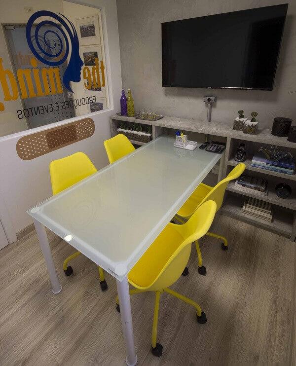 Sala de reunião decorada com mesa branca e cadeira de escritório amarela