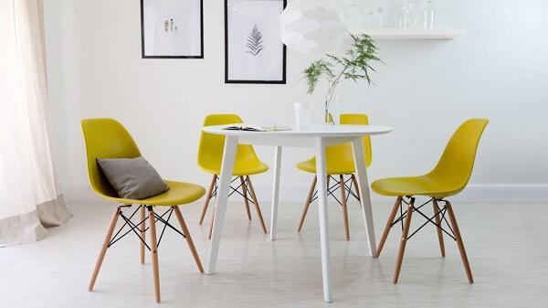 Sala de jantar com mesa branca e cadeira eiffel amarela