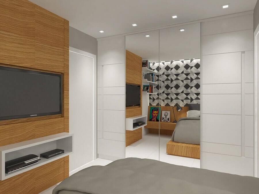 guarda roupa branco com espelho e portas de correr para quarto com painel de madeira Foto Tripper Arquitetura
