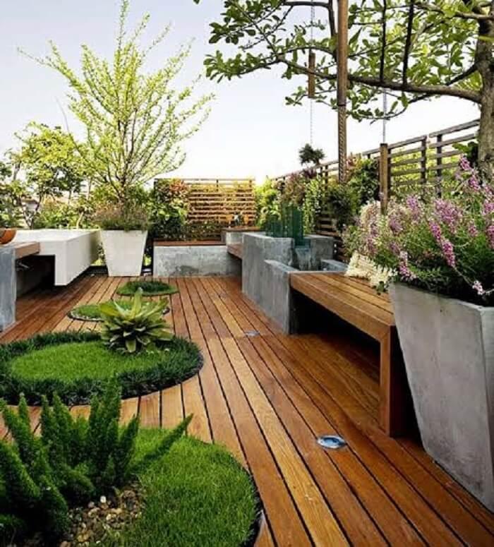 Área de lazer pequena com deck de madeira e grama preta