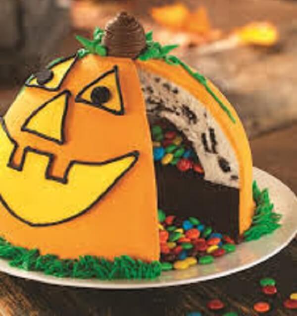 Bolo de Halloween com desenho de abóbora e camada de confete