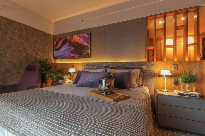 melhor travesseiro - abajur, poltrona rosa, almofadas e quadros decorativos