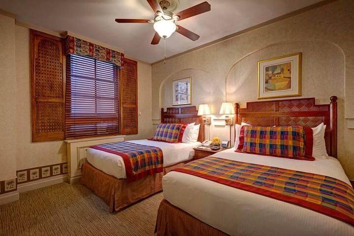 melhor travesseiro - cama com cabeceira de madeira e ventilador de teto