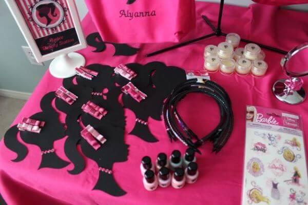 Mesa com maquiagens e presilhas de cabelo na festa da barbie