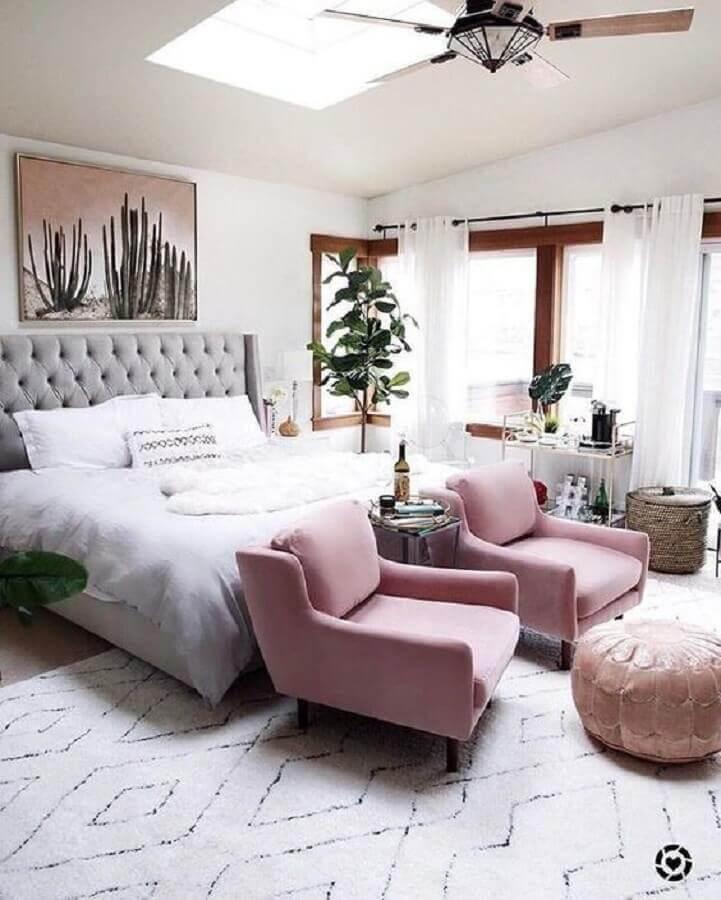 poltrona com puff para quarto de casal amplo decorado com vaso de planta grande Foto Article