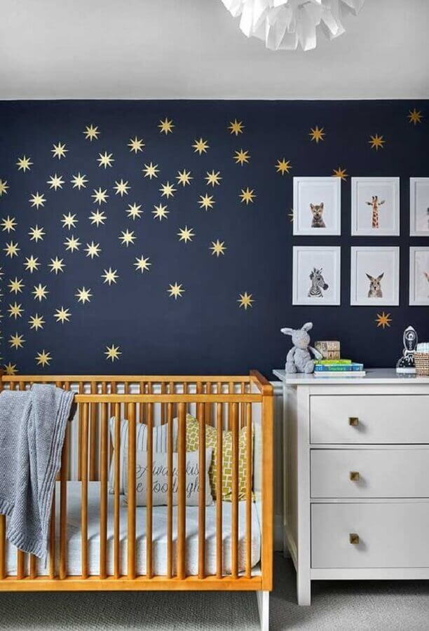quarto de bebê azul marinho com berço de madeira e estrelinhas douradas na parede Foto Ideias Decor
