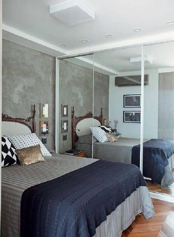 quarto de casal decorado com parede de cimento queimado e guarda roupa com espelho Foto Ideias Decor