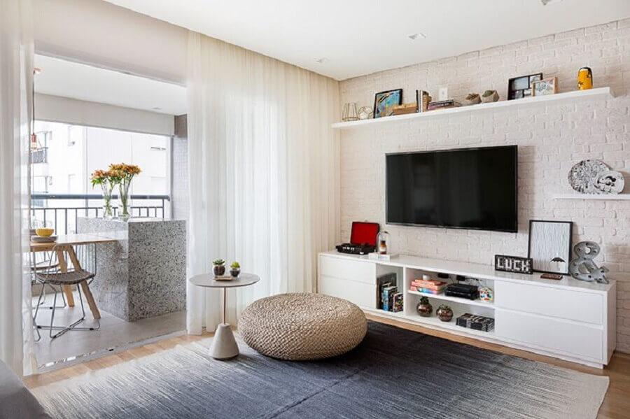 rack para sala pequena decorada com puff redondo e parede de tijolinho Foto Doob Arquitetura