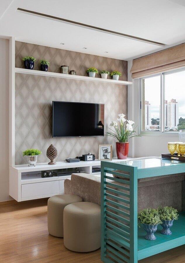 rack suspenso para sala pequena decorada com puff redondo e papel de parede Foto Claudia Comparin