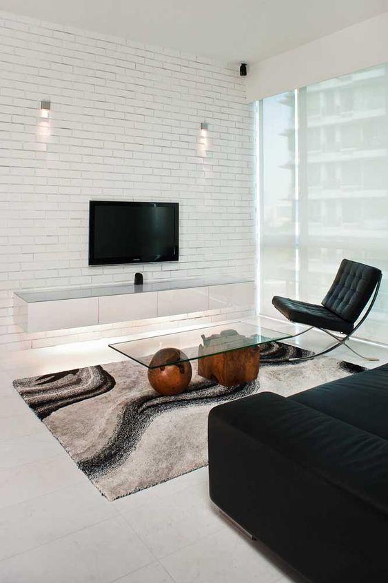 sala de estar com rack suspenso branco em parede de tijolos