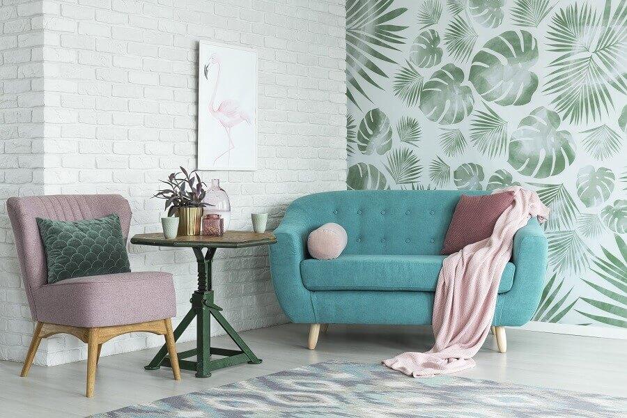 sala de estar decorada com sofá azul e papel de parede com folhagens