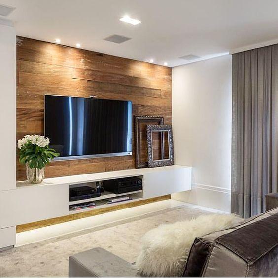 sala de tv com painel em madeira de demolição e rack suspenso branco