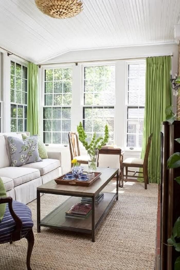Sala de estar com decoração clean conta com cortinas em tom verde e tapete de sisal