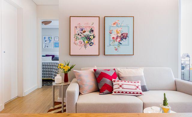 sofá para apartamento - sala pequena com sofá cinza e quadros rosa e azul