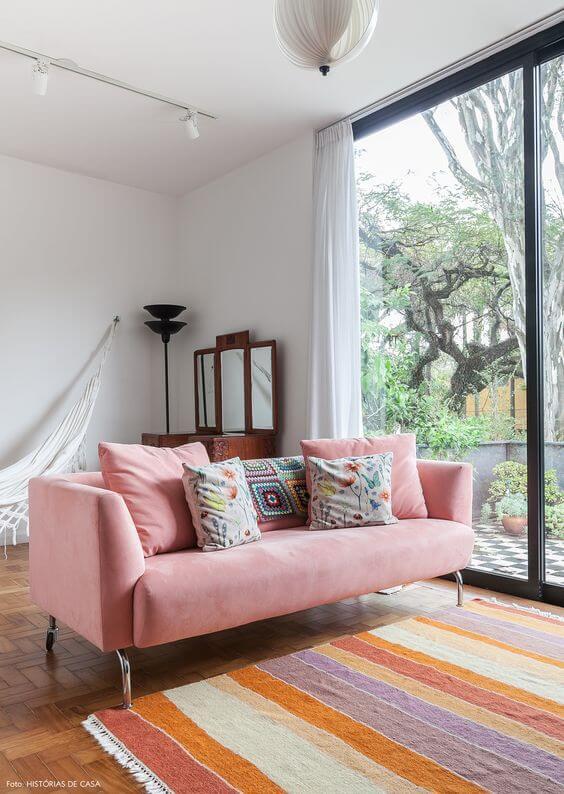 Sofá colorido cor de rosa claro no mesmo tom que o tapete