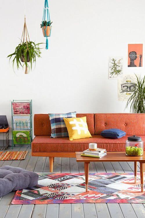 Sofá colorido laranja com almofada azul