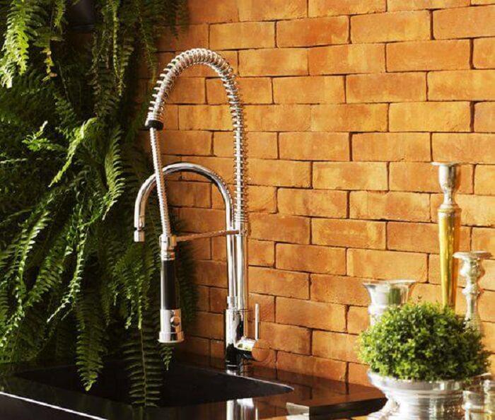 Cozinha com parede tijolinhos e torneira gourmet