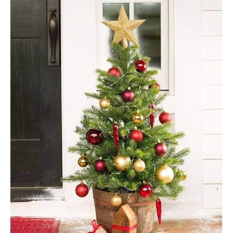 árvore de Natal pequena decorada com enfeites vermelhos e dourados Foto Birch Lane