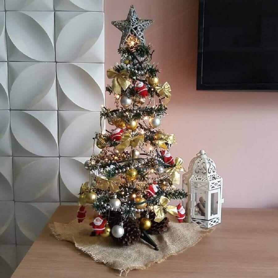 árvore de natal pequena decorada com bolas e laços dourados e pequenos papais noeis Foto Criatividarte