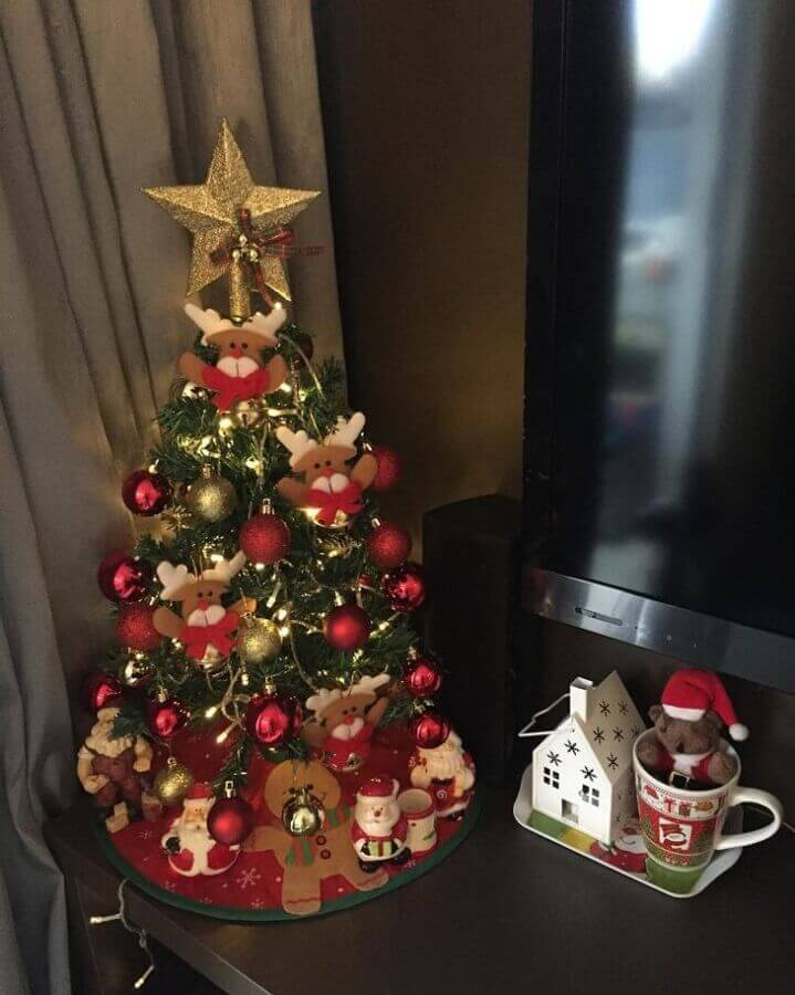 árvore de natal pequena decorada com bolas vermelhas e douradas e renas Foto Casa das Driks