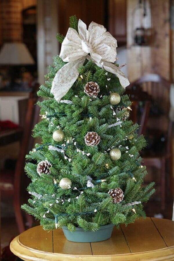 árvore de natal pequena decorada com pinhas e laço no topo Foto Loris Decoration