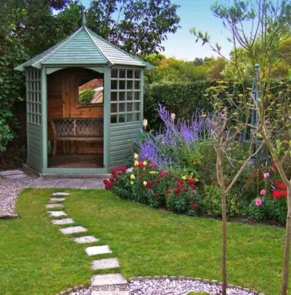 A estrutura em madeira com banco foi utilizada como enfeite de jardim nesse espaço