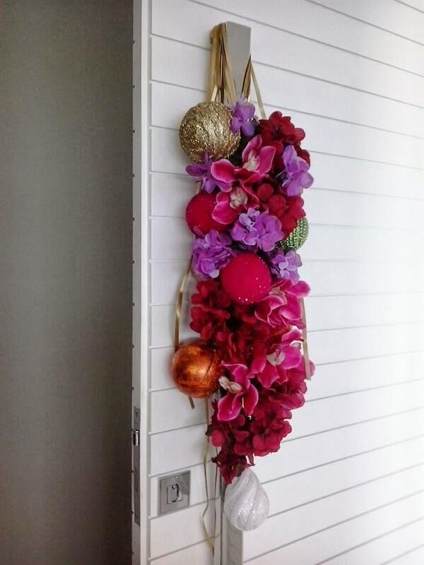 Enfeite de porta para natal feito com flores e posicionado na maçaneta