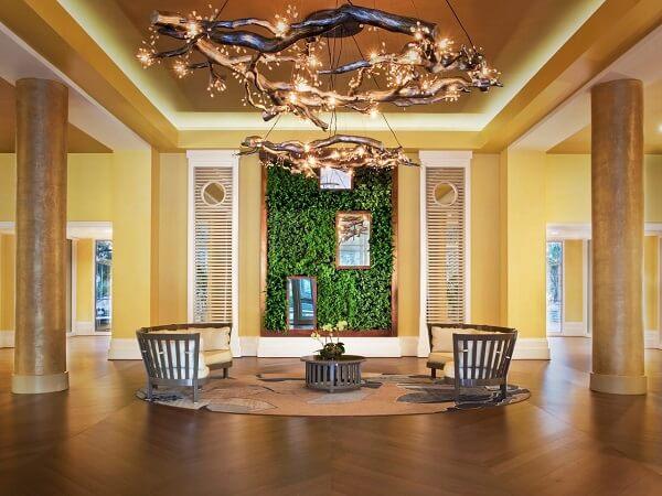 Sala ampla com jardim vertical artificial na parede