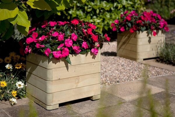 Os vasos de madeira formam lindos enfeites para jardim