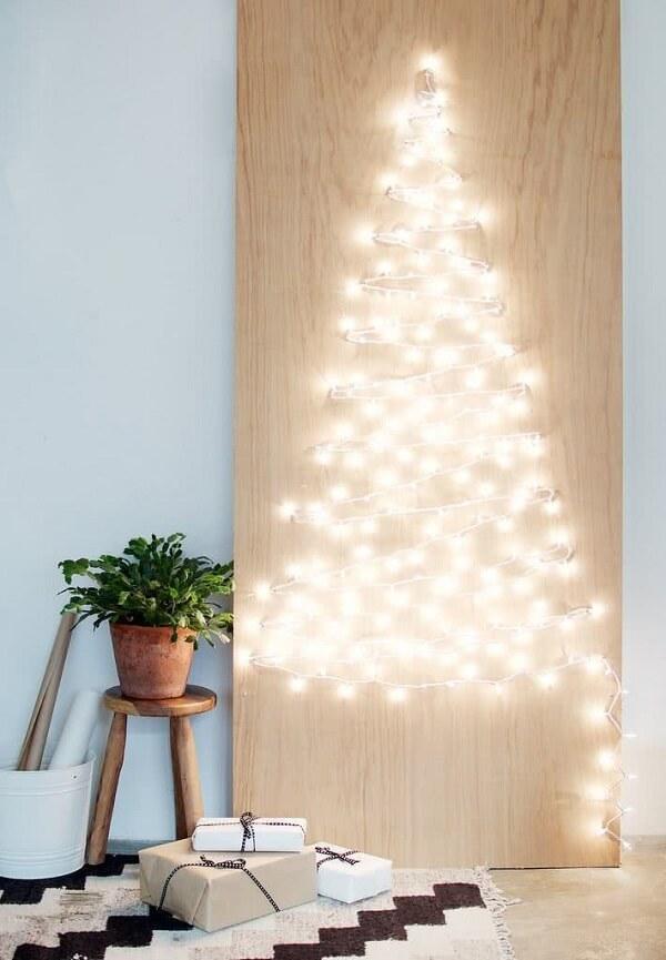 A árvore de Natal na parede foi feita com pisca pisca