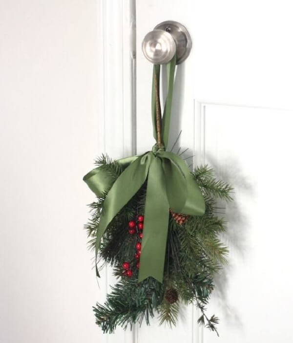 Enfeite de natal para porta feito com ramos e posicionado na maçaneta