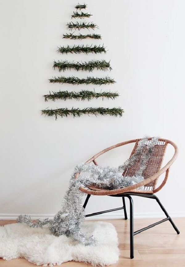 Árvore de Natal na parede feita com galhos naturais