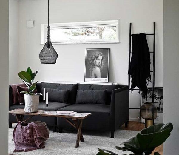 Sala de estar com sofá suede em tom preto de dois lugares