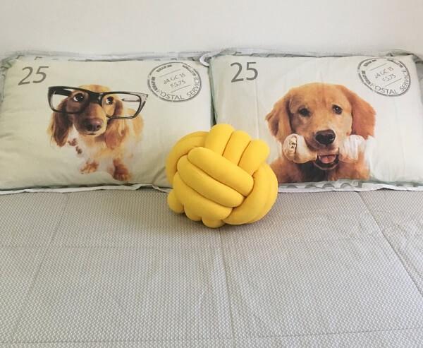 A almofada de nó amarelo sobre a cama trazalegria para o ambiente