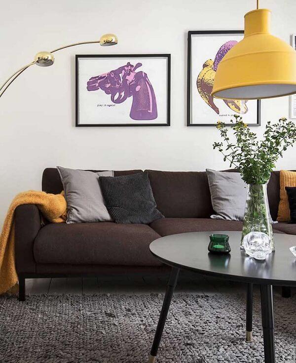 Sala de estar com sofá suede e pendente em tom amarelo