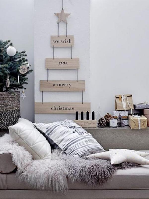 A árvore de Natal na parede foi feita com estrutura de madeira e frases