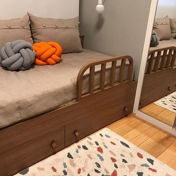 Almofada do tipo nó em tom laranja e cinza decoram o quarto