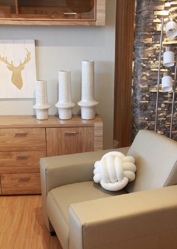 Almofada do tipo nó branca combina com outros detalhes de decoração do ambiente