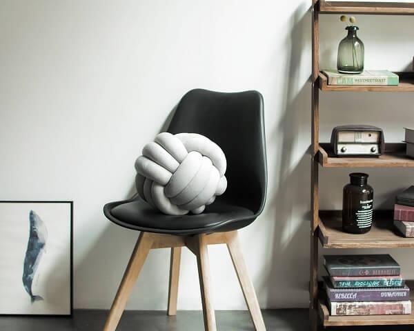 A almofada do tipo nó branca se destaca sobre a cadeira preta