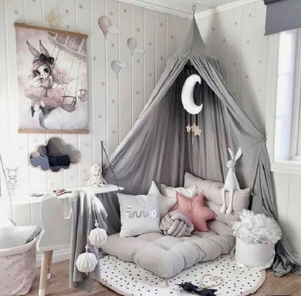 A almofada de nó cinza complementa a decoração do quarto infantil